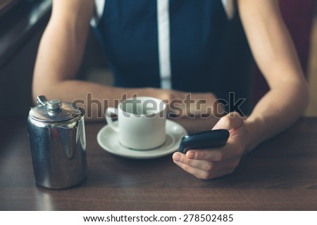 A young woman is having a cup of coffee in a diner and is using her smartphone - stock photo