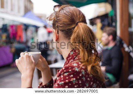 A young woman is having a cup of coffee outside at a table on the street