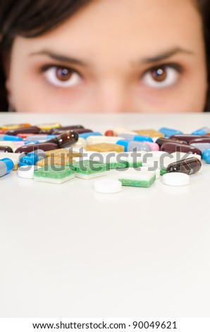 A young woman is hiding behind a table with drugs - stock photo