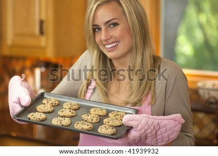 A young woman is holding a baking sheet of cookies and smiling at the camera.  Horizontally framed shot. - stock photo