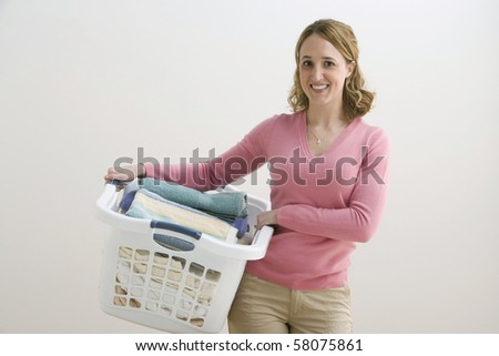 A young woman is holding a basket of folded laundry and smiling at the camera. Horizontal shot.
