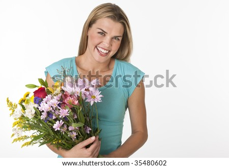 A young woman is holding a boquet of flowers and is smiling at the camera.  Horizontally framed shot.