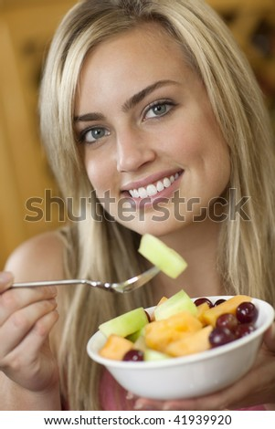 A young woman is holding a bowl of fruit and smiling at the camera.  Vertically framed shot. - stock photo