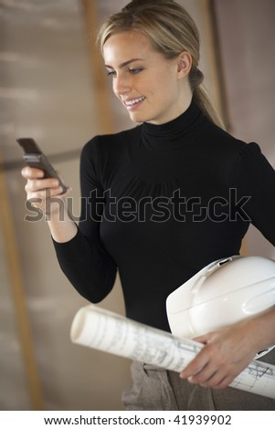 A young woman is holding a cell phone, a hardhat, and blueprints.  She is smiling and looking at the phone.  Vertically framed shot. - stock photo