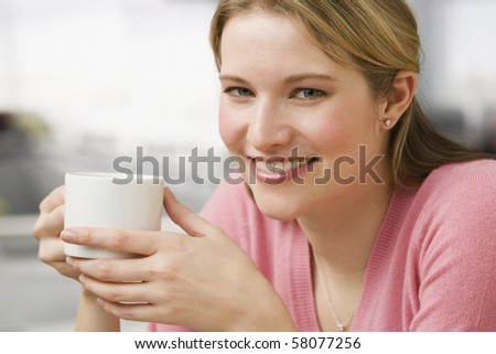 A young woman is holding a coffee cup while smiling at the camera.  Horizontal shot. - stock photo