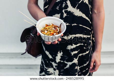 A young woman is holding a paper bowl of grilled squid - stock photo