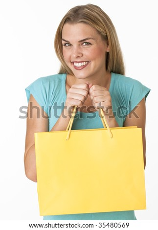 A young woman is holding a shopping bag and smiling at the camera.  Vertically framed shot.
