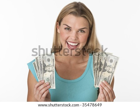 A young woman is holding cash in her hands and smiling at the camera.  Horizontally framed shot.