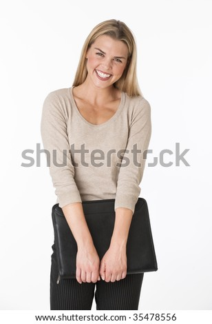 A young woman is holding onto a notebook.  She is smiling at the camera.  Vertically framed shot. - stock photo