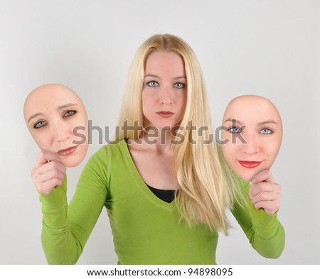 A young woman is holding two mask of herself. One is happy and the other is sad or depressed. use it for a makeover or self esteem concept. - stock photo