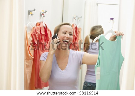A young woman is holding up a dress in a store while talking on a cell phone.  Horizontal shot. - stock photo