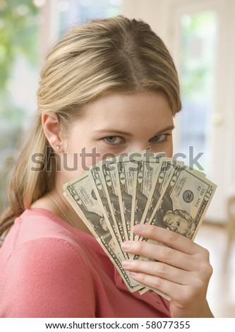 A young woman is holding up cash as a fan while obstructing her face.  Verticalshot.