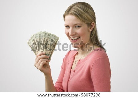 A young woman is holding up cash in a fan and smiling at the camera.  Horizontal shot. - stock photo