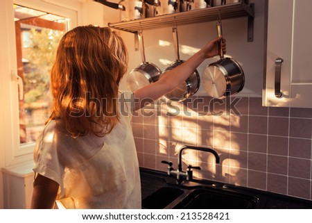 A young woman is in a kitchen and is cooking with a saucepan - stock photo
