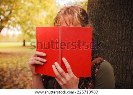 A young woman is in the park on a sunny autumn day and is hiding behind a book - stock photo