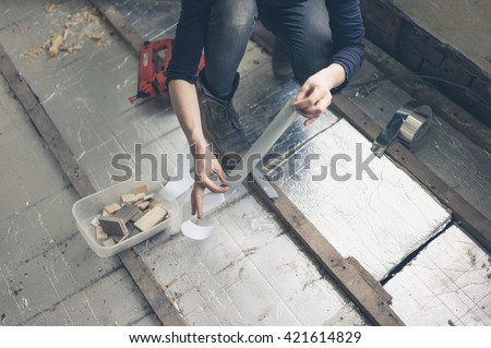 A young woman is insulating the floor with boards and taping them together