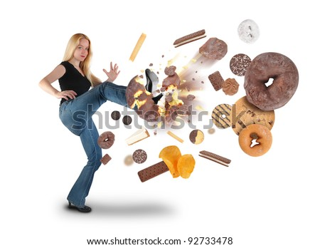 A young woman is kicking a donut on a white background within an assortment of junk food. There are cookies, chips and ice cream. Use it for a diet or nutrition concept. - stock photo