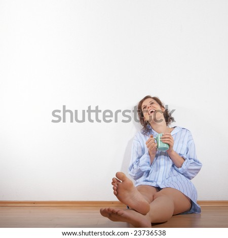 A young woman is laughing and relaxing while drinking her first cup of coffee in the morning in her new appartment. A lot of copyspace left. - stock photo