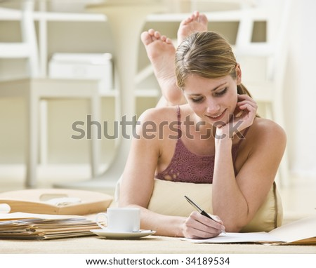 A young woman is laying on her stomach and working on paperwork.  She is looking away from the camera.  Horizontally framed shot. - stock photo