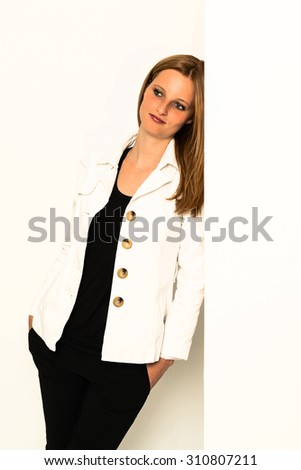 A young woman is leaning against an empty white wall with copy space - bright studio shot - stock photo