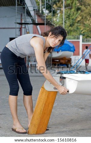 A young woman is leaning over and fixing something on her sailboat.  She is smiling lightly and looking at the camera.  Vertically framed shot. - stock photo
