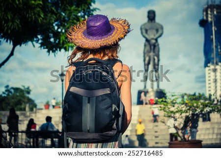 A young woman is looking at a statue in Manila - stock photo