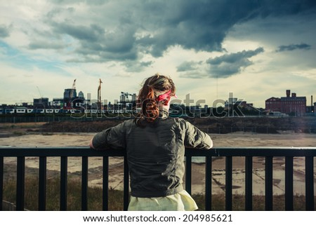 A young woman is looking at a vast  construction site with city in the distance - stock photo