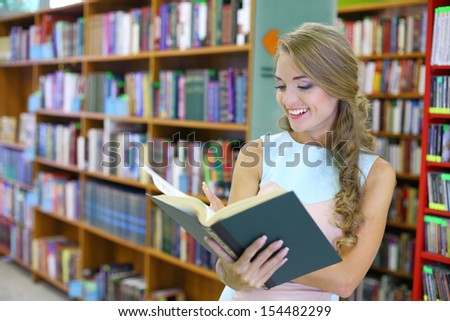 A young woman is looking joyfully into a book among the bookshelves in the library