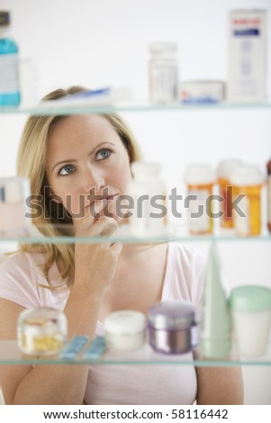 A young woman is looking through her medicine cabinet.  Vertical shot.