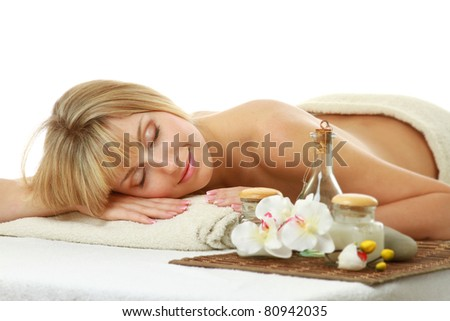 A young woman is lying during a spa treatment on a towel - on white background - stock photo