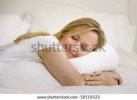 A young woman is lying on her bed with her eyes closed.  She is embracing a pillow.  Horizontal shot.