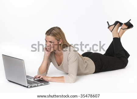 A young woman is lying on the floor and working on a laptop.  She is smiling and looking at the screen.  Horizontally framed shot. - stock photo