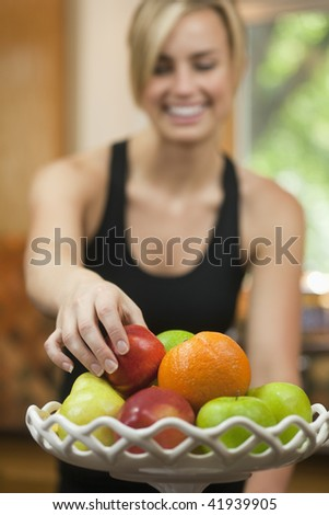A young woman is picking up a piece of fruit, smiling, and looking away from the camera.  Vertically framed shot. - stock photo
