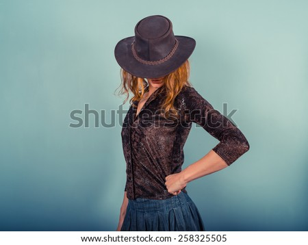 A young woman is posing and wearing a cowboy hat - stock photo