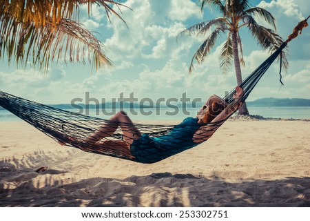 A young woman is relaxing in a hammock on a tropical beach - stock photo