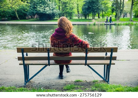 A young woman is sitting and relaxing on a bench in the park by a pond - stock photo