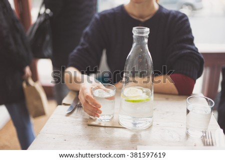 A young woman is sitting at a table in a restaurant and is drinking water - stock photo