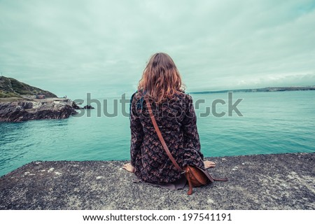 A young woman is sitting by the water's edge in a harbour - stock photo