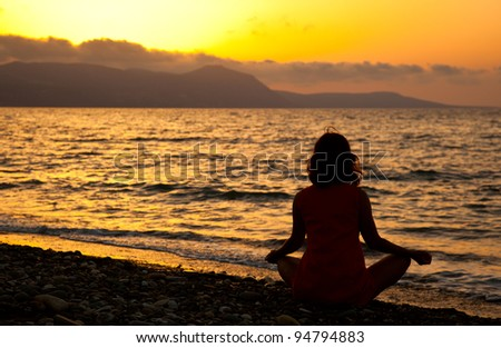 a young woman is sitting in the lotus position on the beach - stock photo