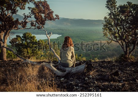 A young woman is sitting on a hill damaged by wild fires at sunrise - stock photo