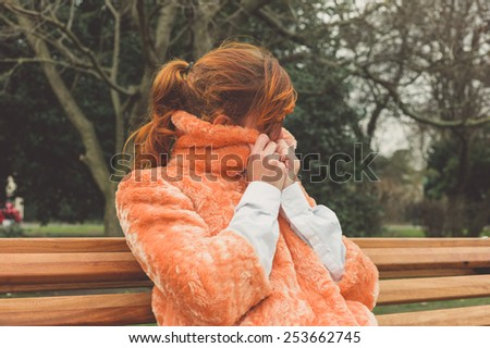 A young woman is sitting on a park bench and is wrapping up in her coat on a winter's day - stock photo