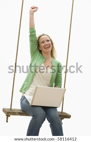 A young woman is sitting on a swing while working on a laptop.  She is raising a fist into the air.  Vertical shot. - stock photo