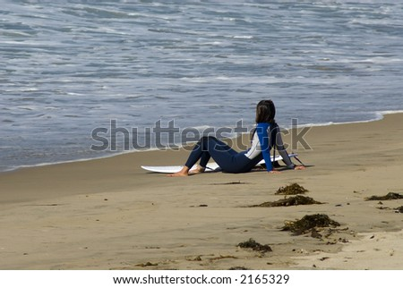 a young woman is sitting on the beach looking at the surf - stock photo