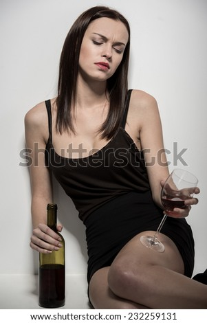A young woman is sitting on the floor with a glass of wine. - stock photo