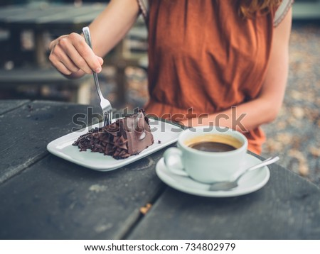 A young woman is sitting outside drinking coffee and eating cake