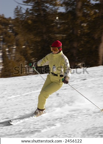 A young woman is skiing at a ski resort at lake Tahoe, California. Background is motion blurred.