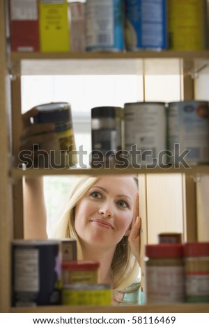 A young woman is smiling as she looks through kitchen cupboards.  Vertical shot. - stock photo
