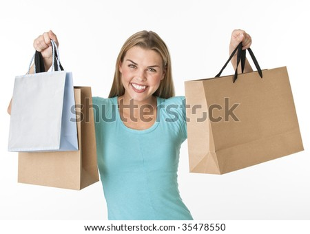 A young woman is standing and holding up shopping bags.  She is smiling at the camera.  Horizontally framed shot.