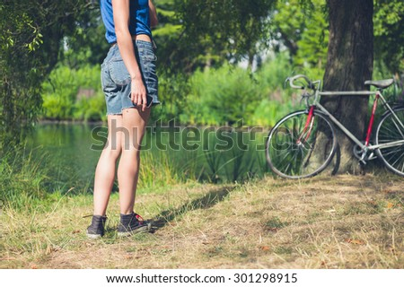 A young woman is standing by the water in a park with her bicycle resting against a tree in the background, she is holding a smart phone in her hand - stock photo