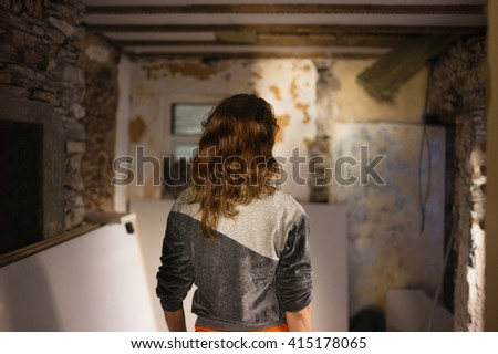 A young woman is standing in a derelict room undergoing renovations